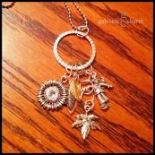 """AUTUMN LEAVES - Hammered stainless steel circle with 6 dangling charms. Pewter sunflower, maple leaf, and scarecrow, and gilded leaves in gold, gunmetal, and copper. 24"""" stainless steel ball chain. $40 as shown."""