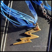 """BOLT - Booster necklace with hand-stamped washer brass lightning bolt. 18"""" navy blue ribbon with stainless steel chain and clasp. $20 as shown."""