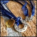 """CHANHASSEN - Booster necklace with single hand-stamped washer with team name. Stainless steel lightning bolt charm, clear plastic initial disc. 18"""" navy blue ribbon with stainless steel chain and clasp. $25 as shown."""