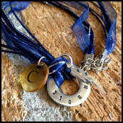 "CHANHASSEN - Booster necklace with single hand-stamped washer with team name. Stainless steel lightning bolt charm, clear plastic initial disc. 18"" navy blue ribbon with stainless steel chain and clasp. $25 as shown."