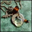"FISHY - Mother's necklace with single washer, hand-stamped with son's name and birthdate. Pewter trout charm, clear acrylic initial disc, Swarovski crystal birthstone trio, amber-colored glass and daisy design pewter beads. 24"" stainless steel ball chain. $50 as shown."