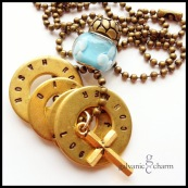 "LDEN - Grandma's necklace with 4 brass washers, each hand-stamped with sets of grandchildren's names. Brass cross, sky-colored glass and textured brass beads. 24"" brass ball chain. $52 as shown."