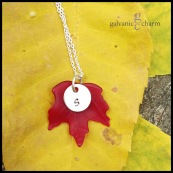 MAPLE LEAF – Dark red resin maple leaf charm with hand-stamped silver-plated circle. 18″ extra fine silver-plated cable chain. $25 as shown.