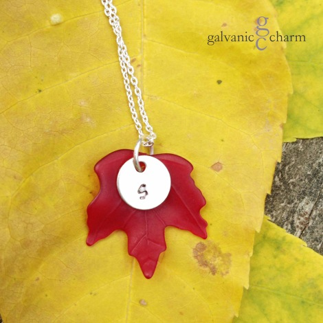 """MAPLE LEAF - Dark red resin maple leaf charm with hand-stamped silver-plated circle. 18"""" extra fine silver-plated cable chain. $25 as shown."""