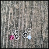"""PEACE GIRL - Girl's necklace with silver-plated peace sign and wire wrapped Swarovski crystal birthstone drop. Shown with pink tourmaline and opal (October). 14"""" fine rhodium-plated ball chain. $20 as shown."""