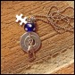 """PUZZLE - Mother's necklace with 2 hand-stamped washers, pewter hockey stick and puzzle piece charms, wire wrapped sterling silver initial, and blue and white polka dot glass bead. 18"""" stainless steel ball chain. $30 as shown."""