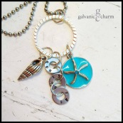 "SUN SAND SEA - 3 hand stamped small washers (sun, sand sea) in 1.5mm uppercase block font, linked onto a silver-plated ring with pewter spiral shell and blue enameled starfish charms. 20"" stainless steel ball chain. $40 as shown."