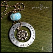 "SUNFLOWER - Mother's necklace with hand-stamped 35mm washer in 3mm lowercase Bridgette font.. Pewter sunflower charm, sky blue glass bead. 20"" weathered stainless steel ball chain. $45 as shown."