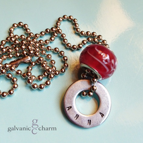 "ANNA - Child's necklace with single hand-stamped washer. Cherry-colored glass bead. 16"" stainless steel ball chain. $22 as shown. Available directly or on Etsy."