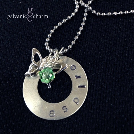 "ASPIRE - Charm necklace with 1"" German silver washer, hand-stamped ""aspire."" Pewter butterfly charm and wire wrapped light green Swarovski crystal drop. Stainless steel ball chain. $25 as shown."