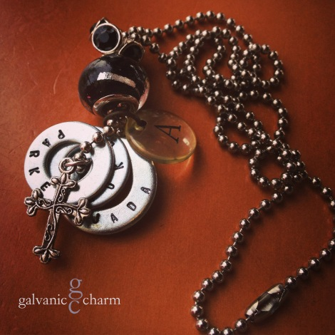 "CHARMER - Mother's necklace with 3 hand-stamped washers. Stainless steel ornate cross, clear acrylic initial disc, black-design glass and black rhinestone beads. 24"" stainless steel ball chain. $45 as shown. Available directly or on Etsy."