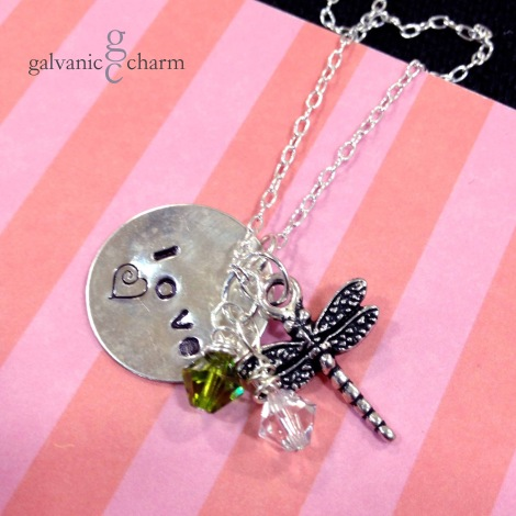 "DRAGONLOVE - Charm necklace with 1"" .925 sterling silver disc, hand-stamped ""love,"" pewter dragonfly charm, and wire wrapped peridot and crystal Swarovski crystal drops. 18"" extra fine cable chain. $35 as shown."