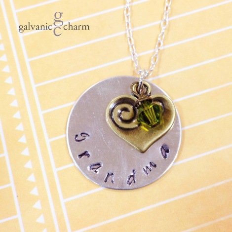 "GRANDMA KAT - Grandma's necklace with a hand-stamped 1"" sterling silver circle, antique brass heart charm, and wire wrapped Swarovski crystal birthstone drop. 18"" silver plated light cable chain. $35 as shown."