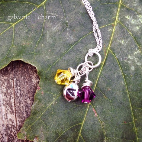 "JOINED - Newlywed necklace with sterling silver wire wrapped initial charm with two wire wrapped Swarovski crystal birthstone drops (pictured with amethyst and citrine). 18"" extra-fine silver-plated cable chain. $25 as shown. Available directly or on Etsy."