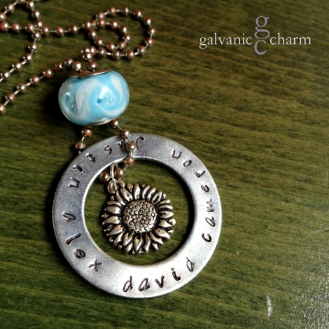 "SUNFLOWER - Mother's necklace with hand-stamped 35mm washer in Bridgette font. Pewter sunflower charm, sky blue glass bead. 20"" weathered stainless steel ball chain. $45 as shown. Available directly or on Etsy."