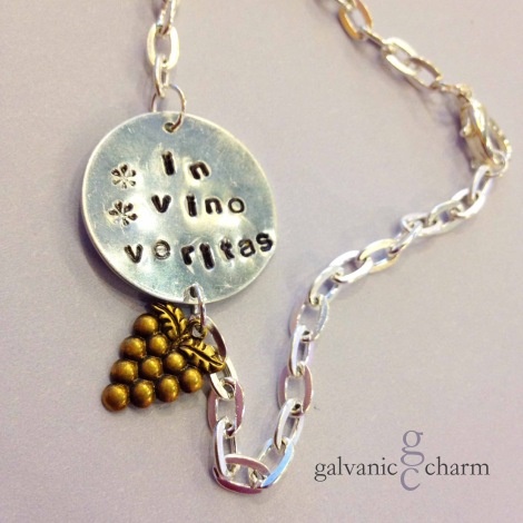 "VERITAS - Charm bracelet with 1"" distressed German silver disc, hand-stamped with ""in vino veritas,"" translated ""in wine is truth,"" and brass grape bunch charm. 3mm lowercase Gothic font. 7.5"" silver plated cable chain."