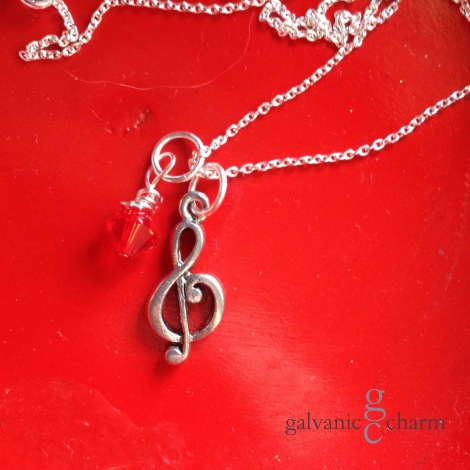 "CLEF - Pewter G-clef charm with wire wrapped Swarovski crystal birthstone drop, pictured in ruby (July). 18"" silver filled light cable chain. $20 as shown. Available directly or on Etsy."