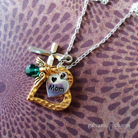 "MOM'S HEART - Memorial necklace with pewter cross and engraved ""mom"" heart charms, 14k gold plated open heart, and gold wire wrapped Swarovski round crystal birthstone drop with brass angel wings. 18"" silver plated light cable chain. $40 as shown."
