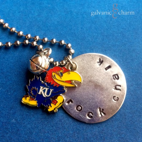 """JAYHAWK - Team necklace with 1"""" nickel silver disc, hand-stamped with """"rock chalk"""" in 3mm lowercase Gothic font. Pewter basketball charm and blue, crimson, and yellow enamel Jayhawk. Stainless steel ball chain. $30 as shown. Available directly or on Etsy."""